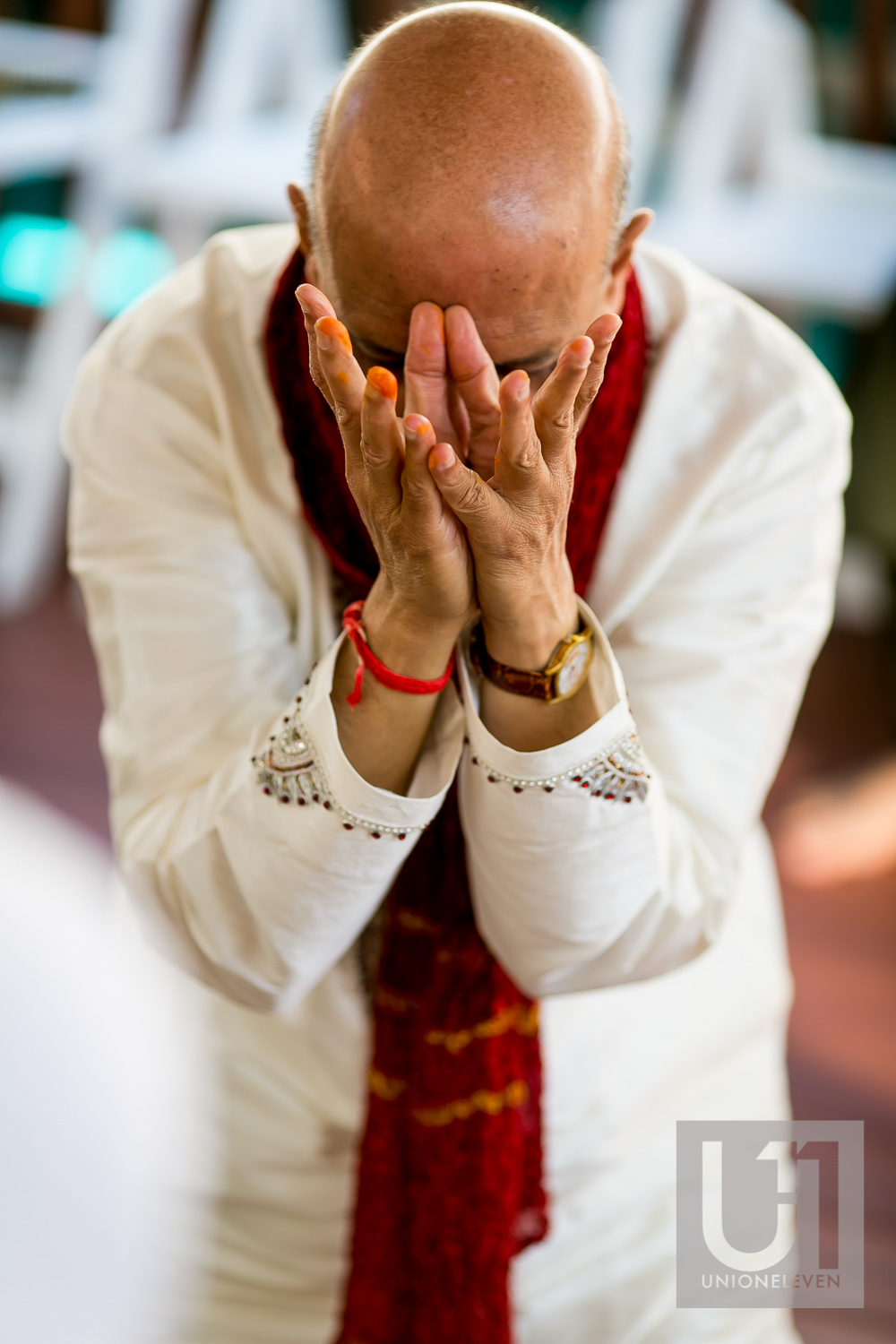 grooms father praying at a mendhi ceremony