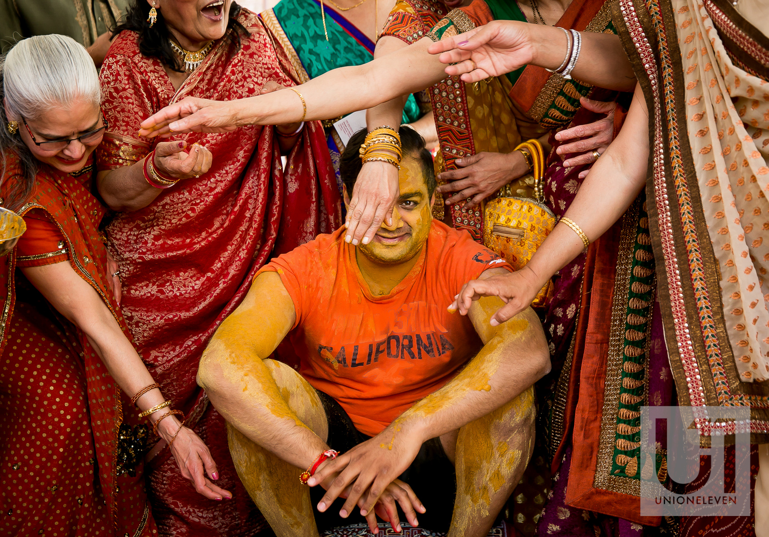 Pithi spice being rubbed all over an indian grooms face at his mendhi party
