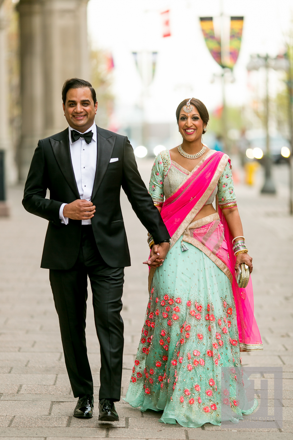 indian couple walking outside of the chateau laurier on their wedding day