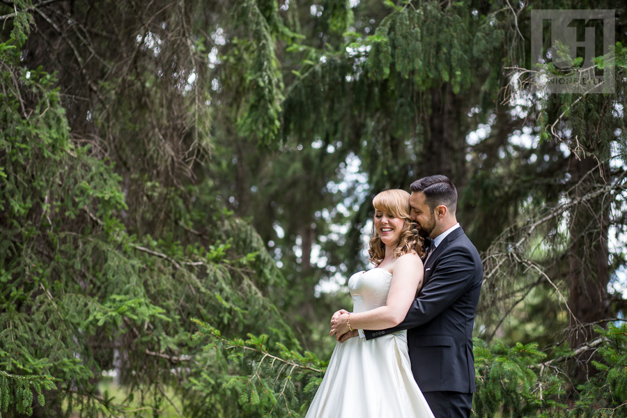 smiling-bride-and-groom-in-back-to-chest-embrace-in-woodsy-area-of-ottawa