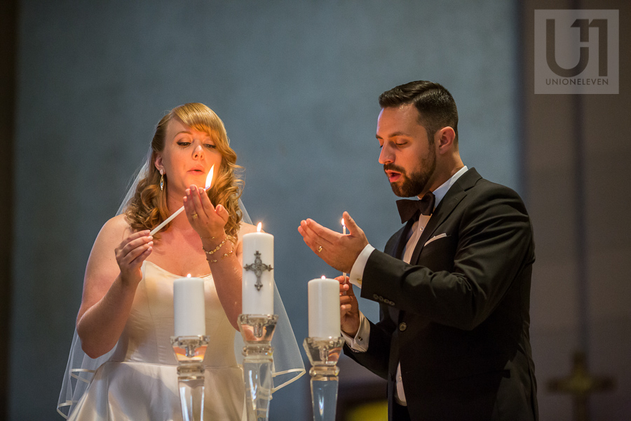 bride-and-groom-blowing-out-flame-after-lighting-candle-inside-ottawa-church-at-wedding