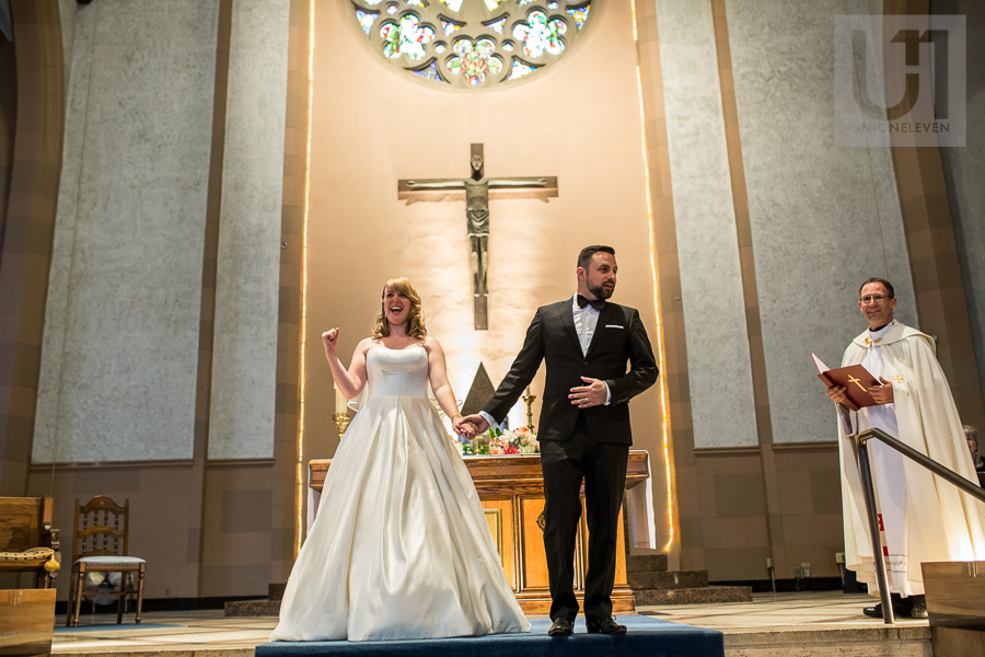 bride-fist-pumping-while-holding-grooms-hand-inside-church-after-ottawa-wedding-ceremony