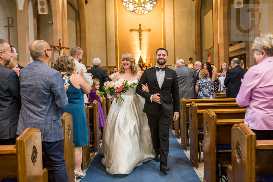 smiling-bride-and-groom-walking-down-church-aisle-as-husband-and-wife-after-ottawa-wedding-ceremony