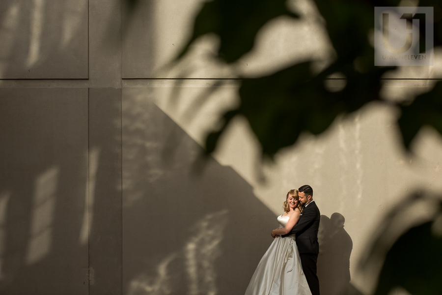 bride-groom-in-back-to-chest-embrace-in-front-of-concrete-wall-downtown-ottawa