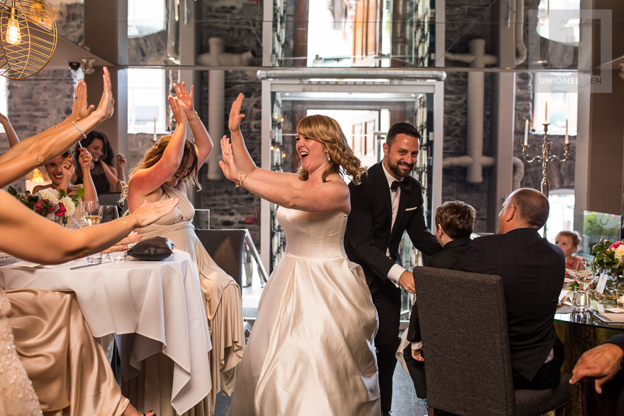 bride-and-groom-high-fiving-guests-while-entering-eighteen-restaurant-for-wedding-reception-in-ottawa