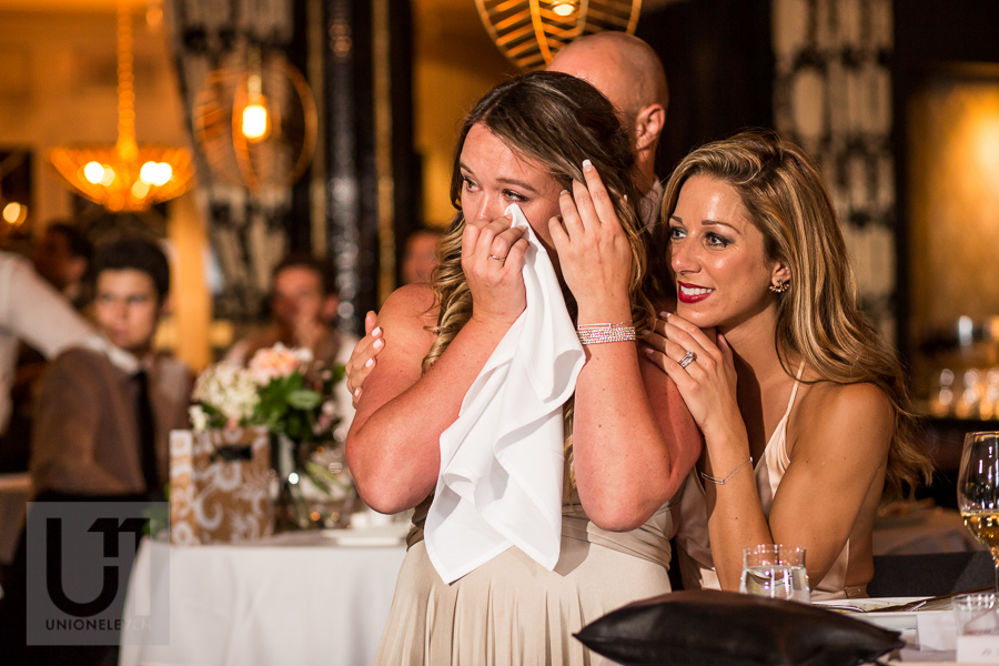 two-bridesmaids-holding-each-other-while-one-cries-during-speeches-at-wedding-reception-at-eighteen-restaurant-in-ottawa