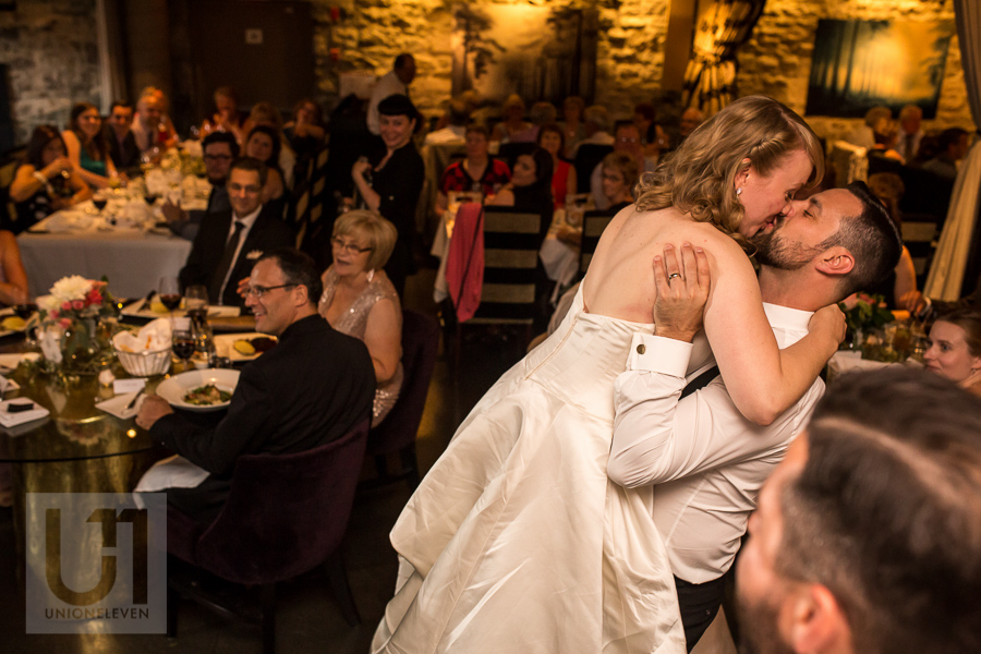 groom-lifting-bride-while-kissing-during-wedding-reception-at-eighteen-restaurant-in-ottawa