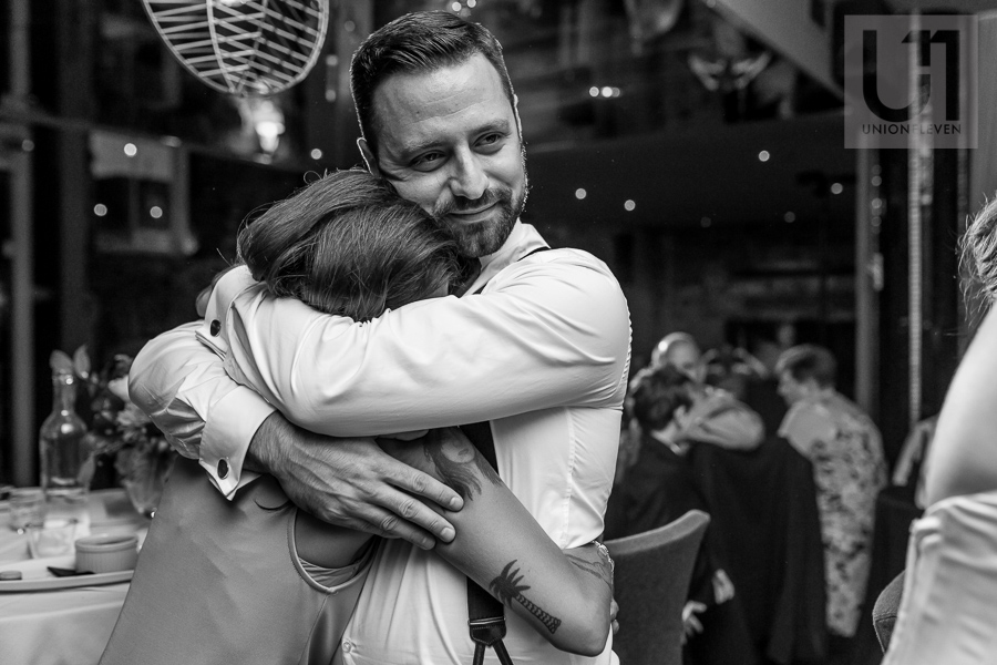 black-and-white-image-of-groom-hugging-bridesmaid-during-wedding-reception-at-eighteen-restaurant-in-ottawa