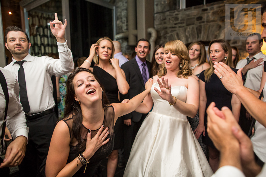 female-guest-fanning-herself-and-pushing-away-bride-while-dancing-during-wedding-reception-at-eighteen-restaurant-in-ottawa