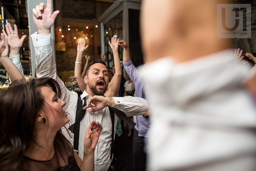 groom-dancing-with-hands-up-along-with-other-guests-during-wedding-reception-at-eighteen-restaurant-in-ottawa