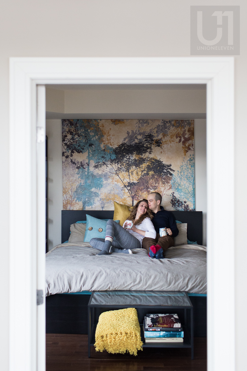 couple-snuggling-on-bed-through-doorframe