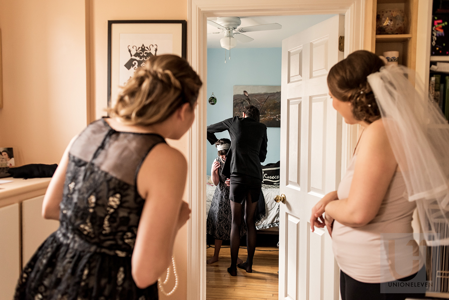 The bride and her Maid of Honour looking over to their bridesmaid getting the final touches of her dress