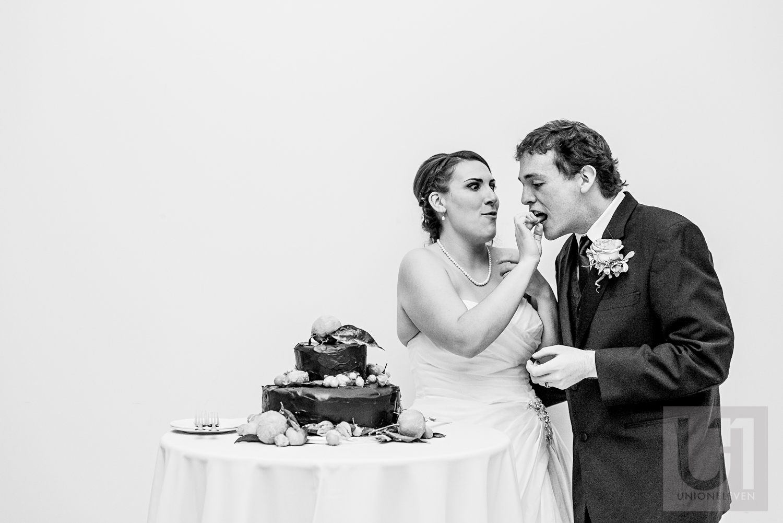 The bride feeding wedding cake to the groom during their wedding reception