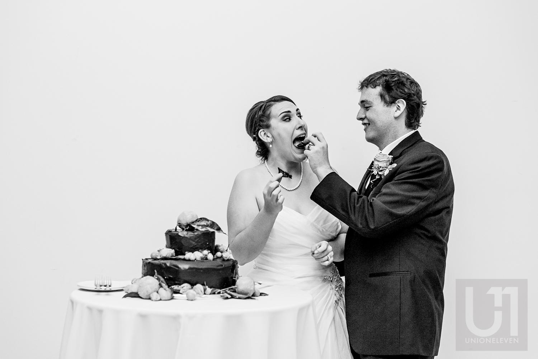 The groom feeding wedding cake to the bride at their wedding reception