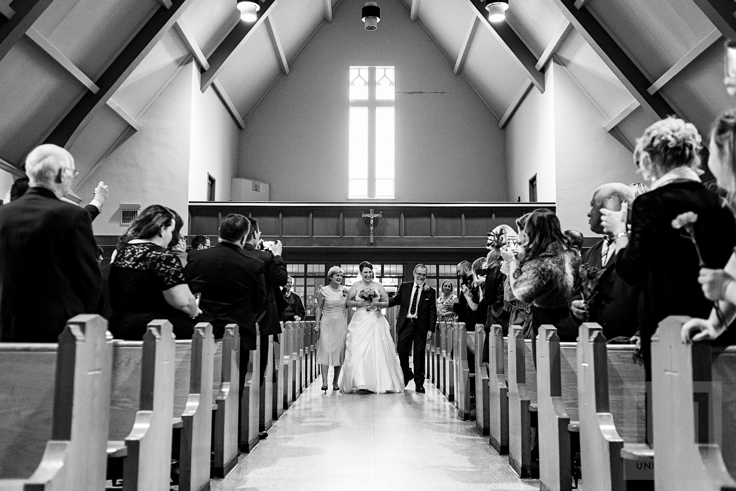 The bride being walked down the aisle by her parents