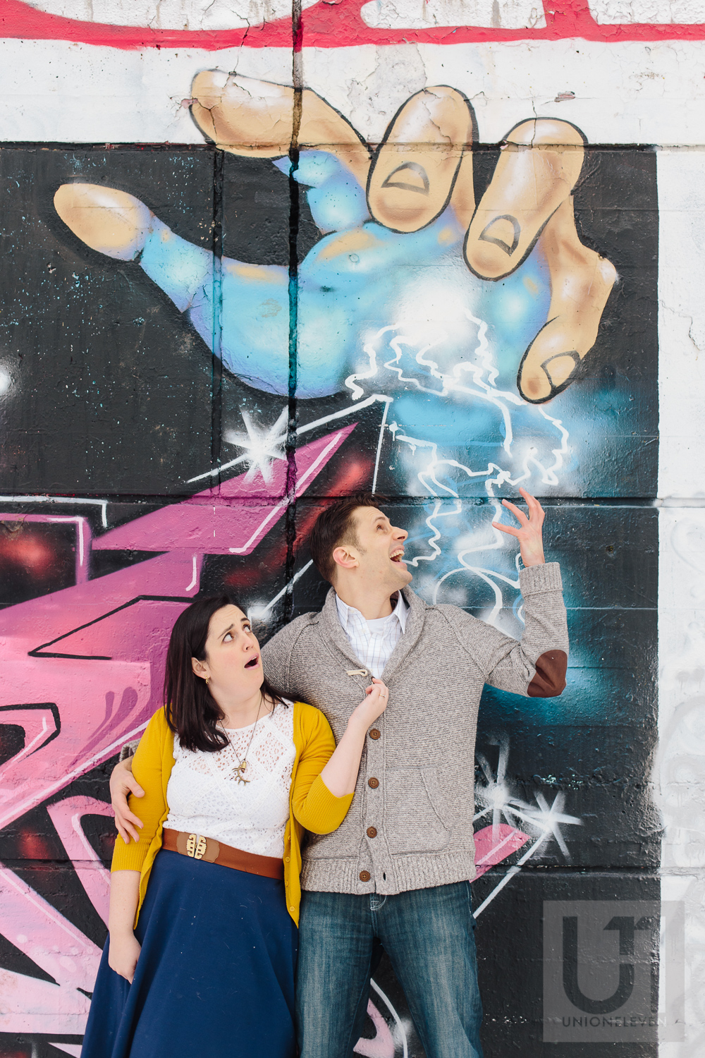 Engagement shoot of the couple doing a dramatic pose in front of a graffiti wall in Ottawa