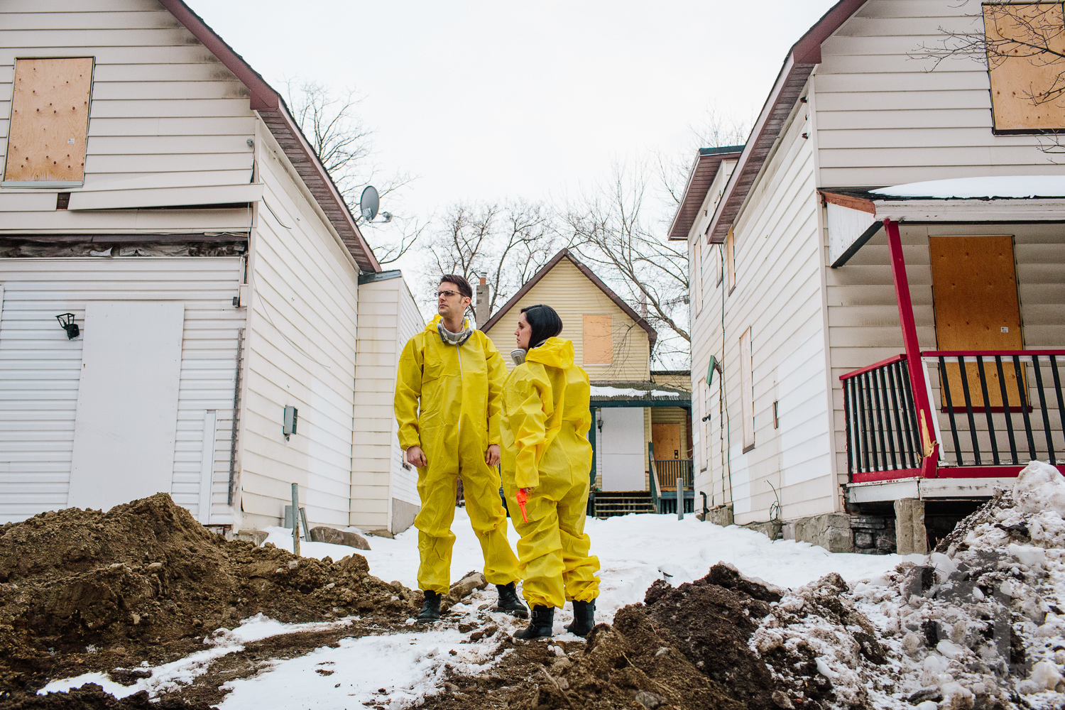 Engagement shoot of the couple doing a dramatic pose dressed in their hazmat suits