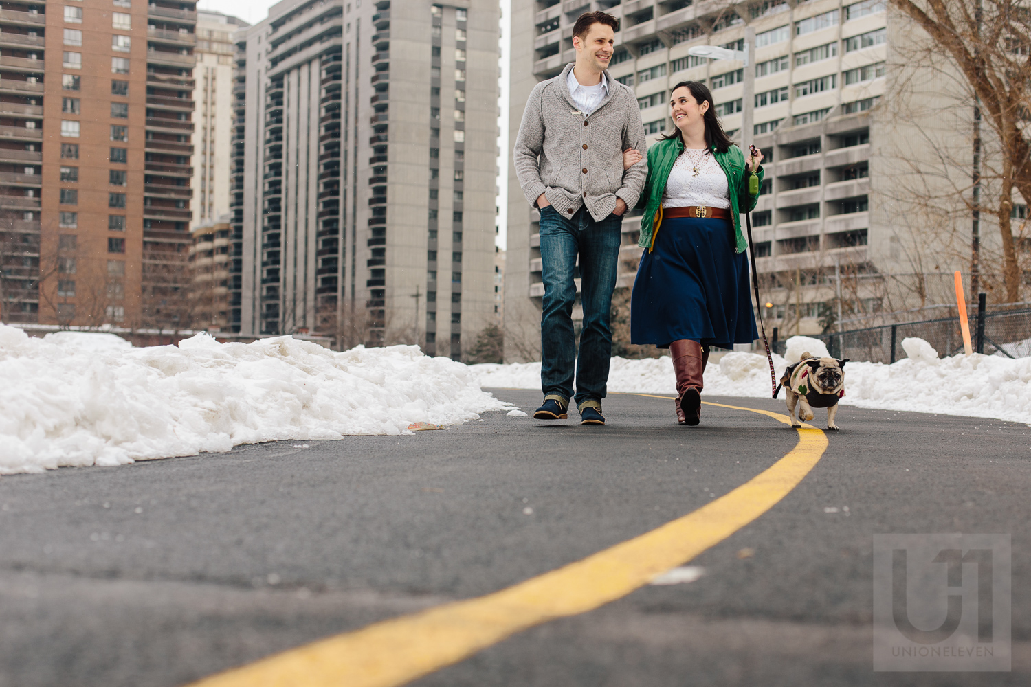 Engagement shoot of the couple and their pug going for a walk in downtown ottawa