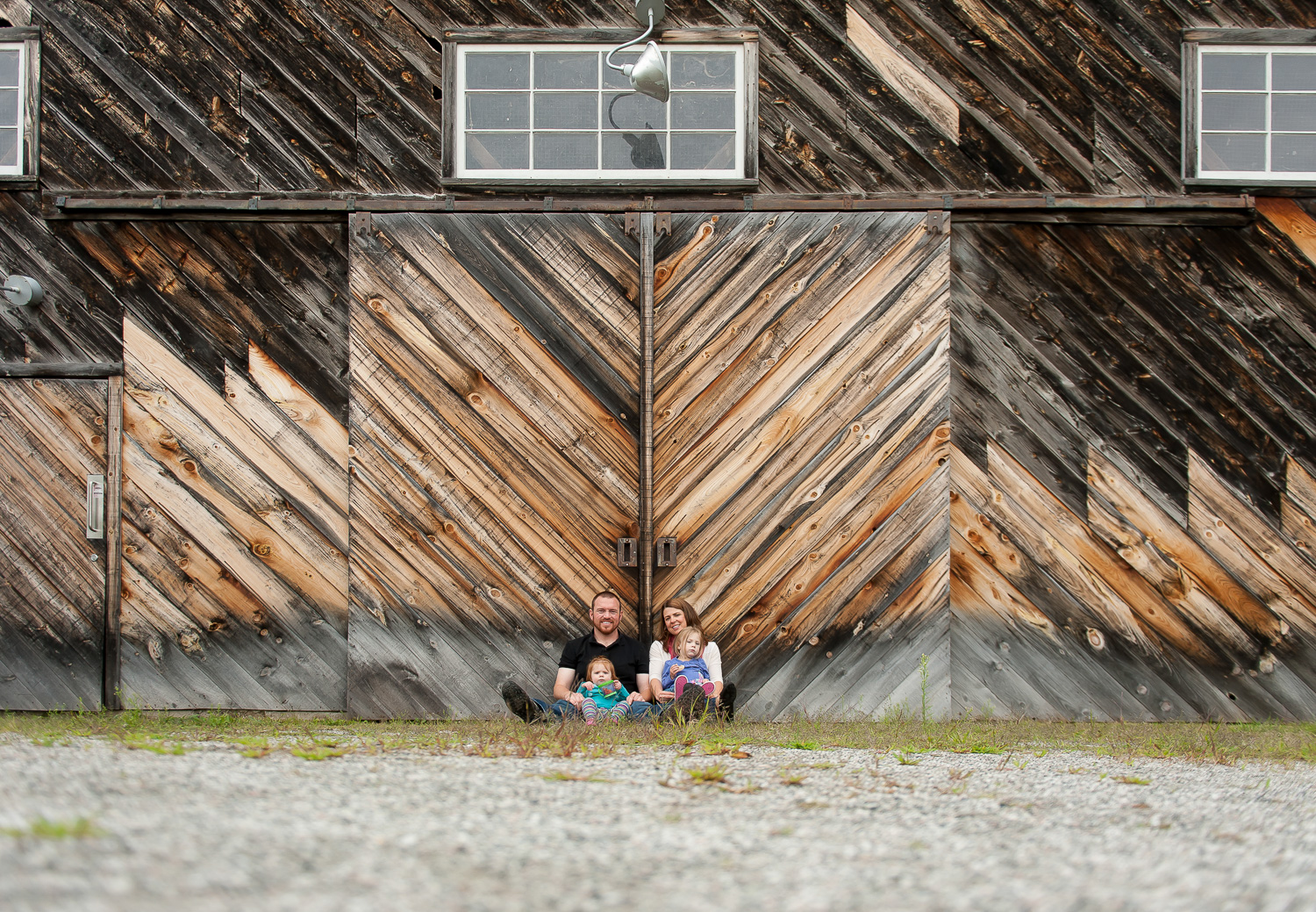 portrait of a family with a baby in front of a barn