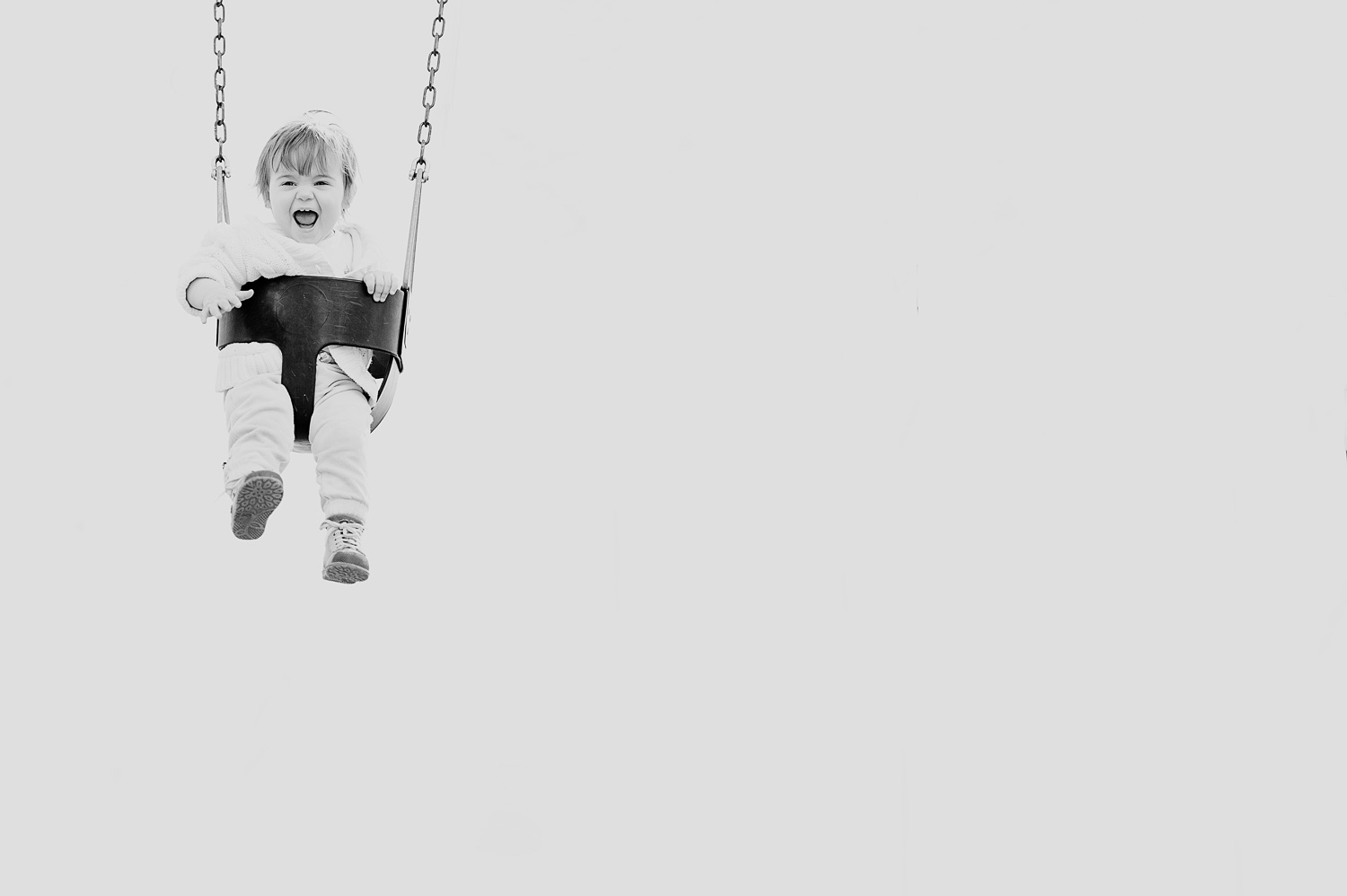 photo of a little baby having fun on a swing