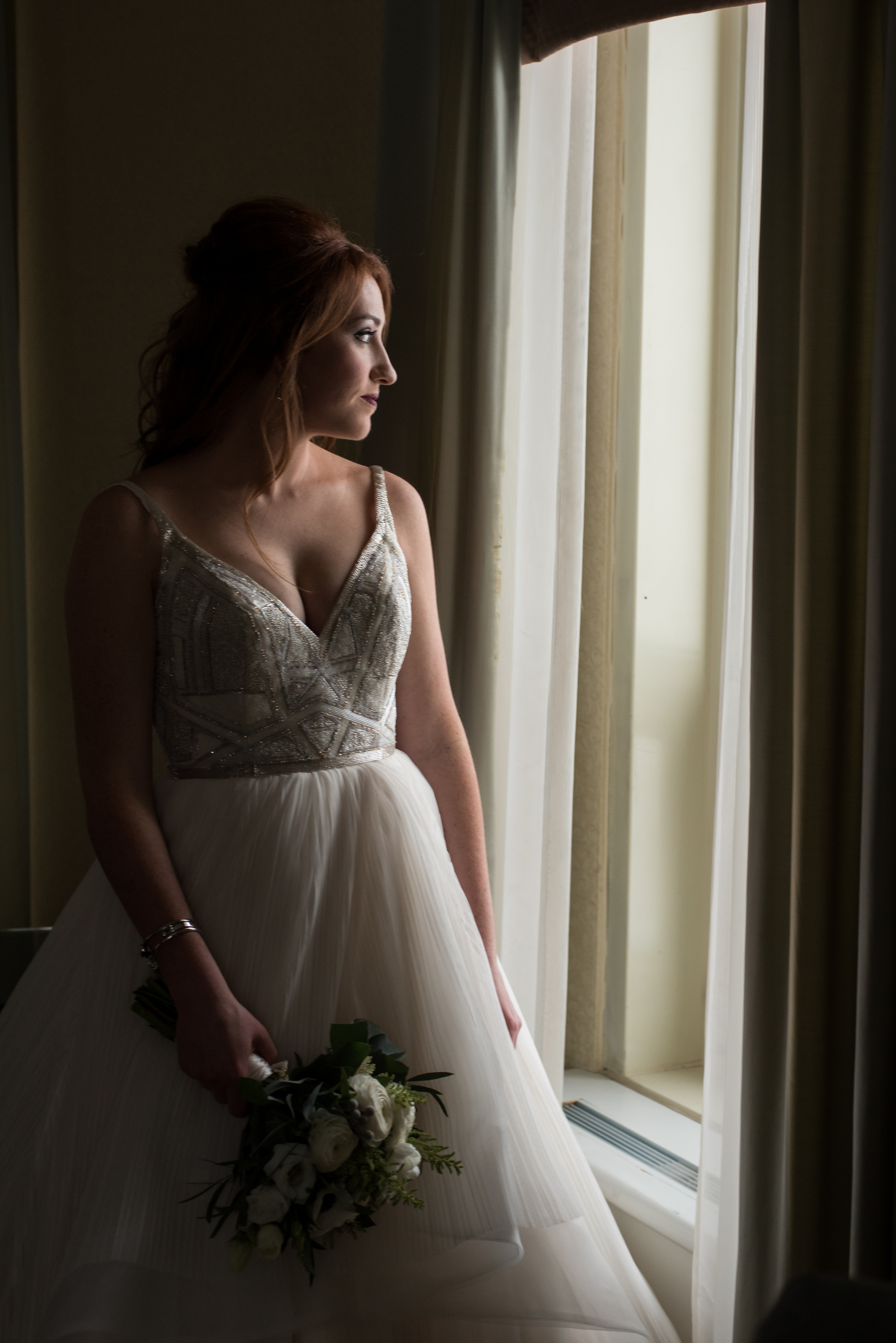 Portrait of the bride in her gown and bouquet gazing out the window
