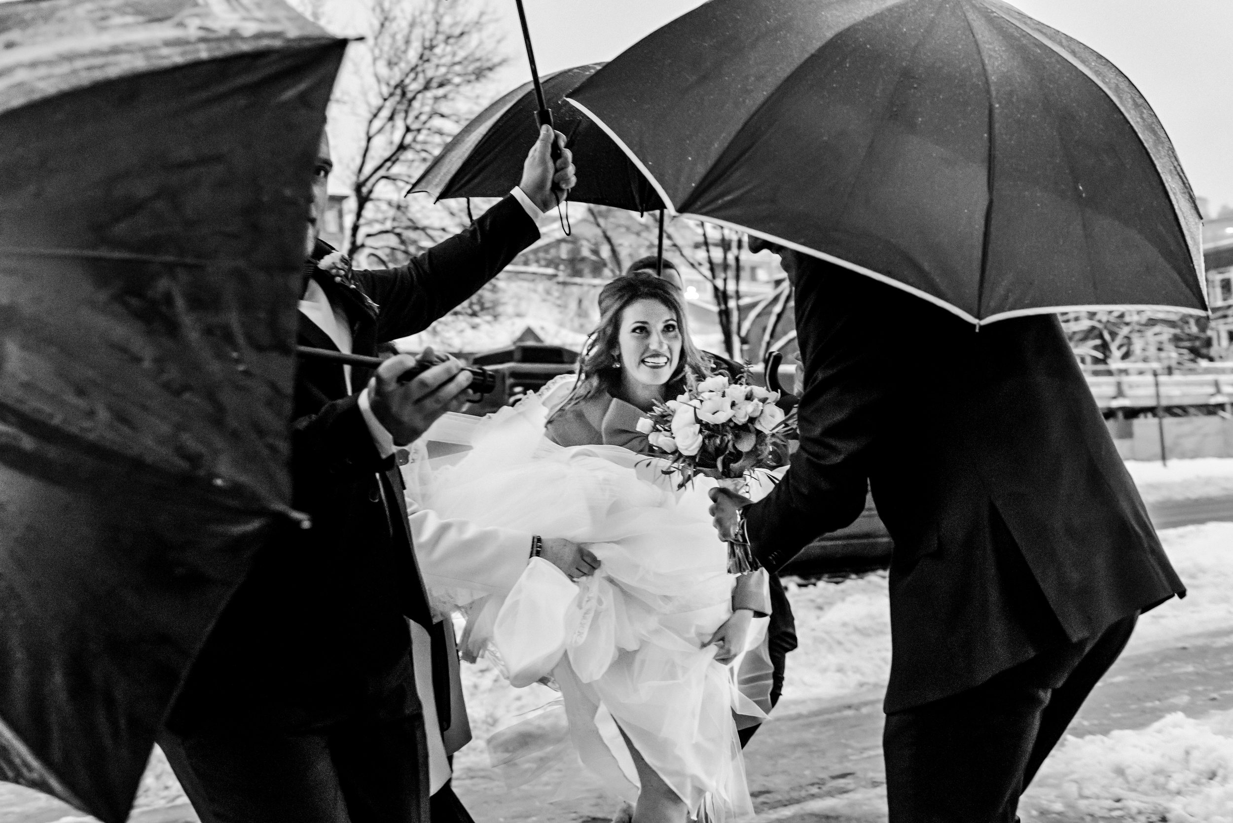 The bride arriving at the ceremony with the groomsmen covering her from the rain with umbrellas