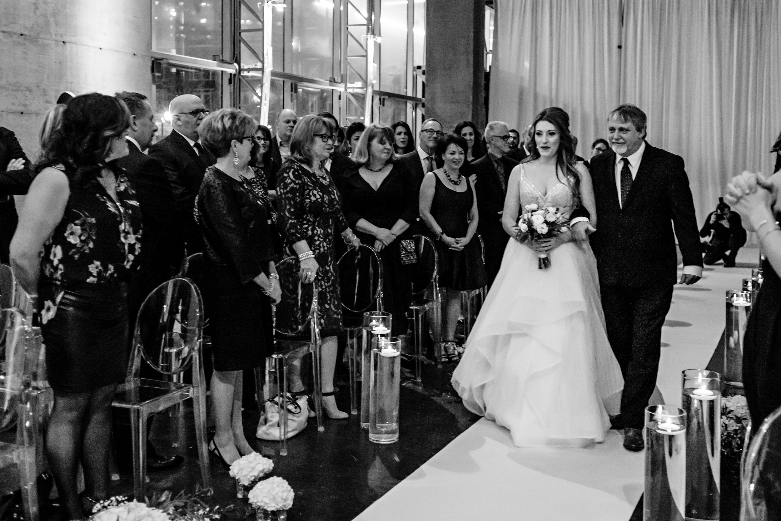 A black and white photo of the bride and her father walking down the aisle