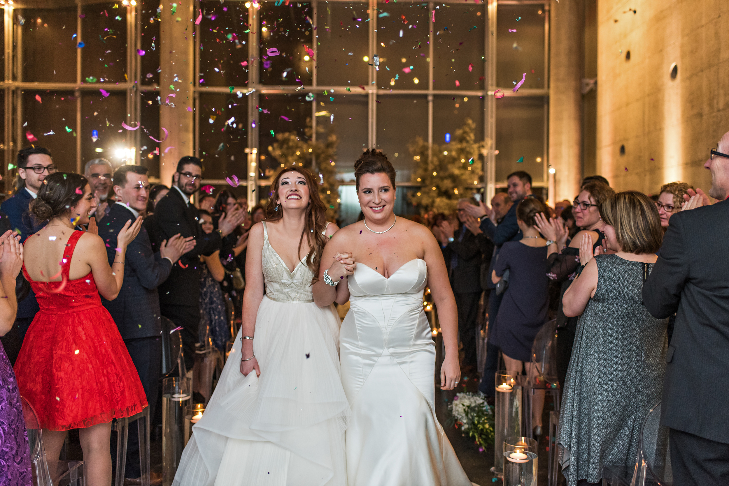 The two brides walking hand in hand leaving their wedding ceremony in Quebec City