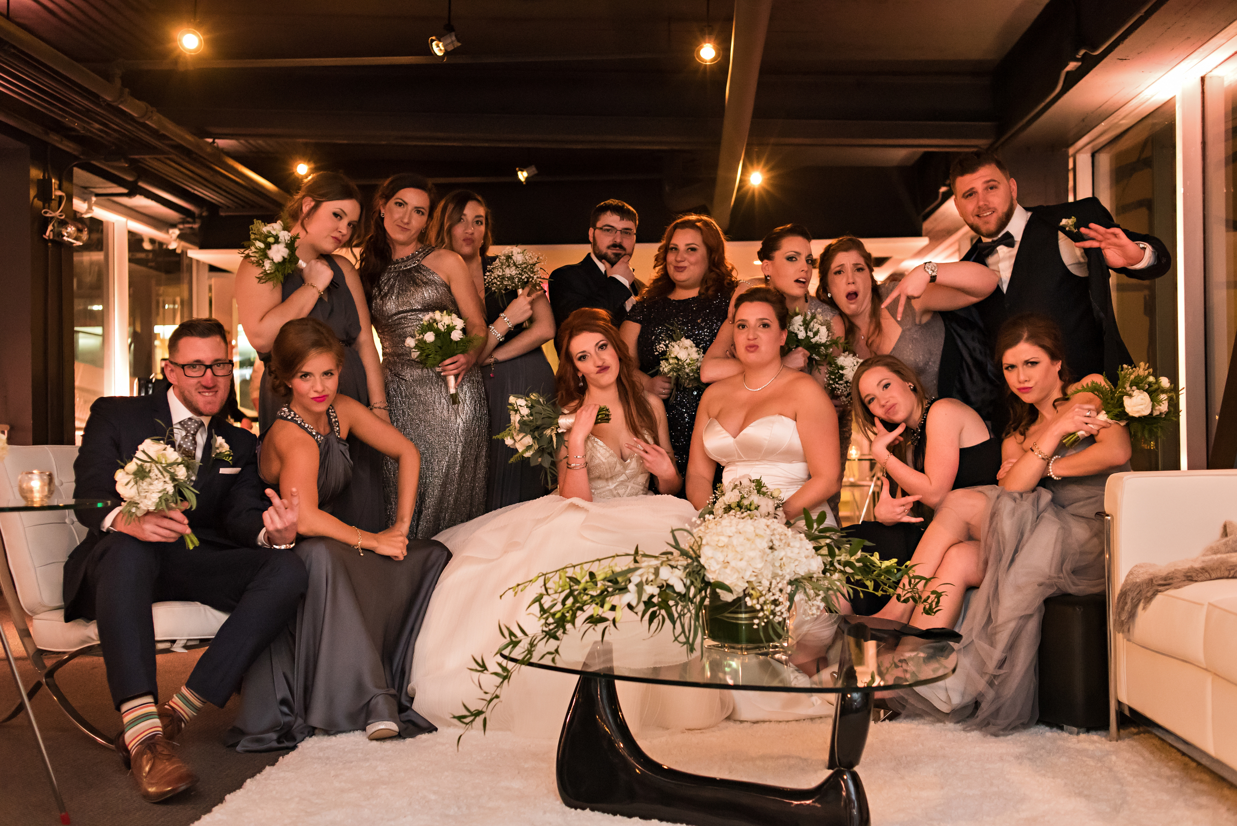 A group photo of the brides and their wedding parties at the wedding reception in Quebec City