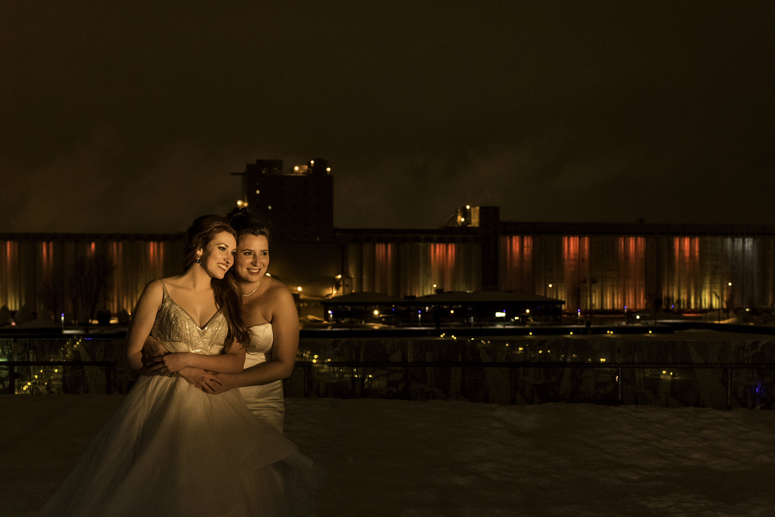 A portrait of the brides on the rooftop outside their wedding reception in Quebec CIty