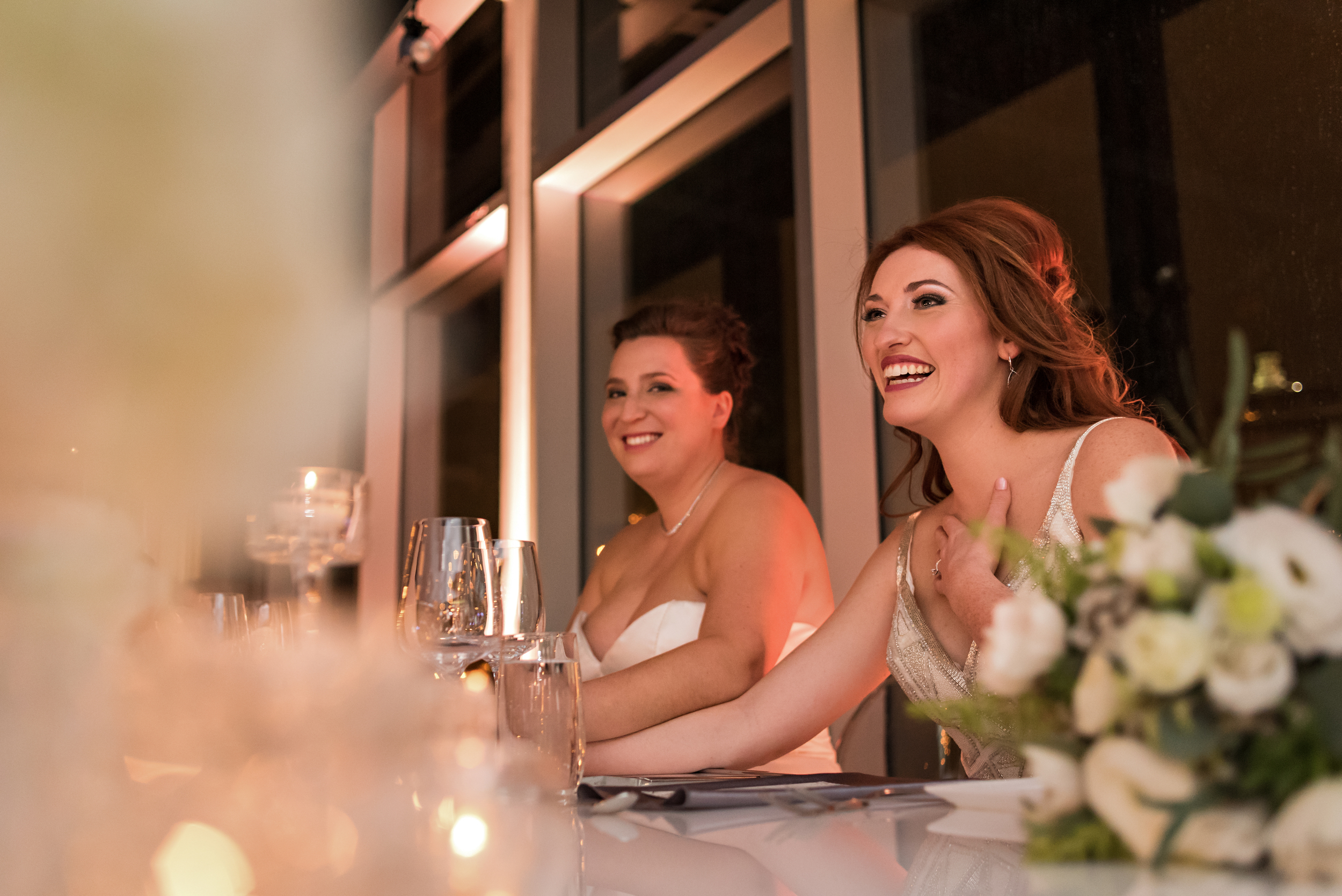 The brides at the head table enjoying the speeches