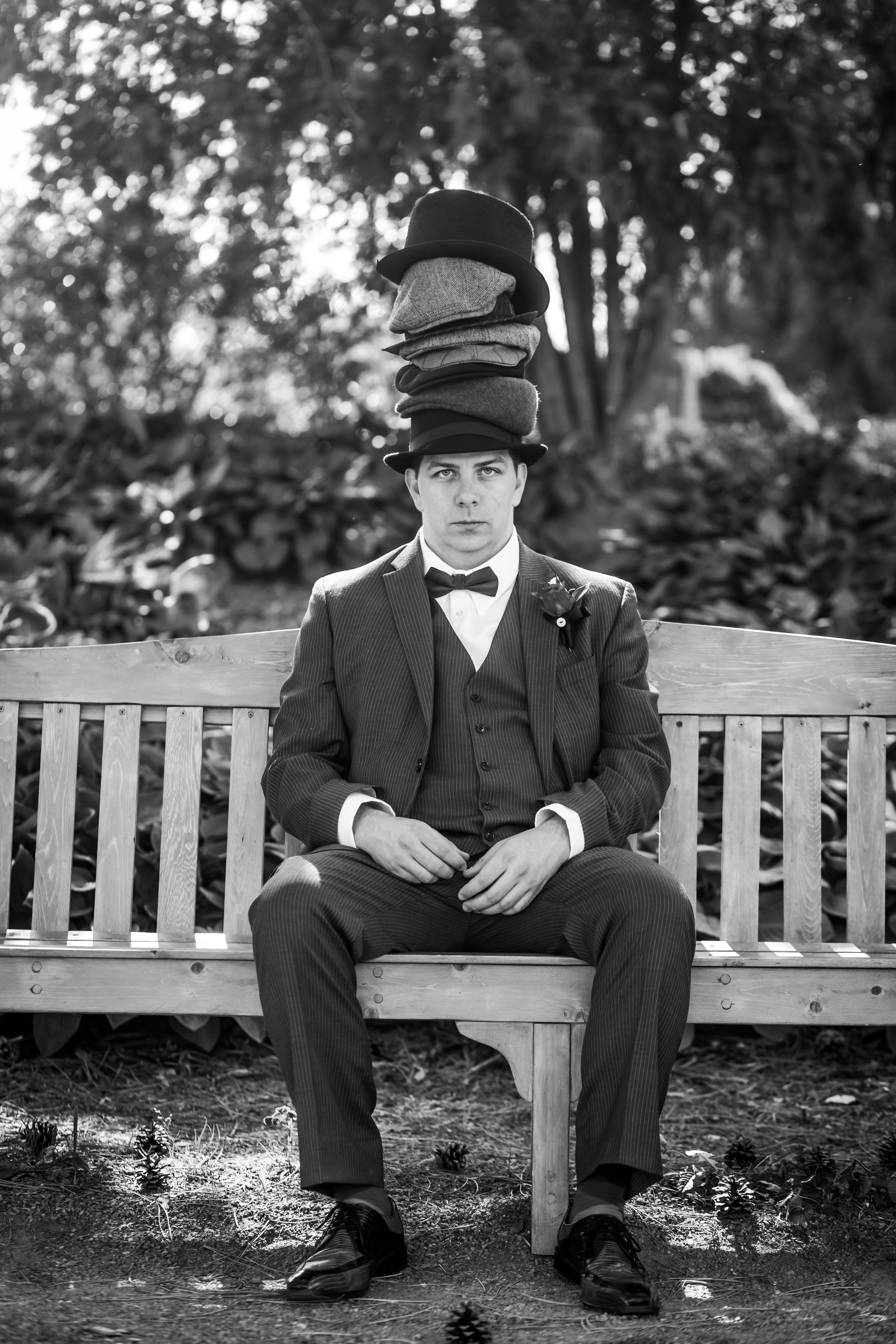 A portrait of the groom seated on a bench wearing a bunch of hats