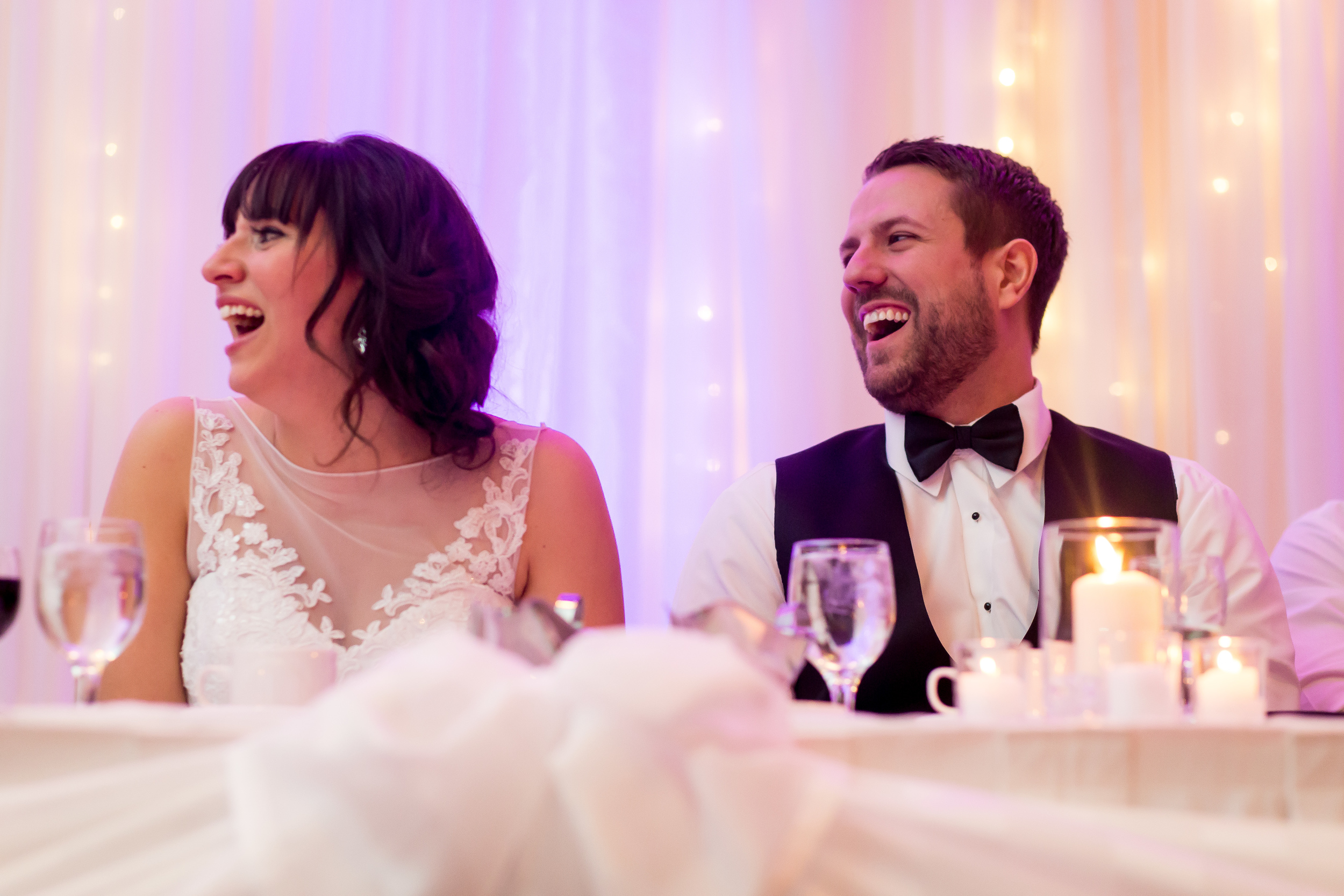 The bride and groom laughing during the speeches