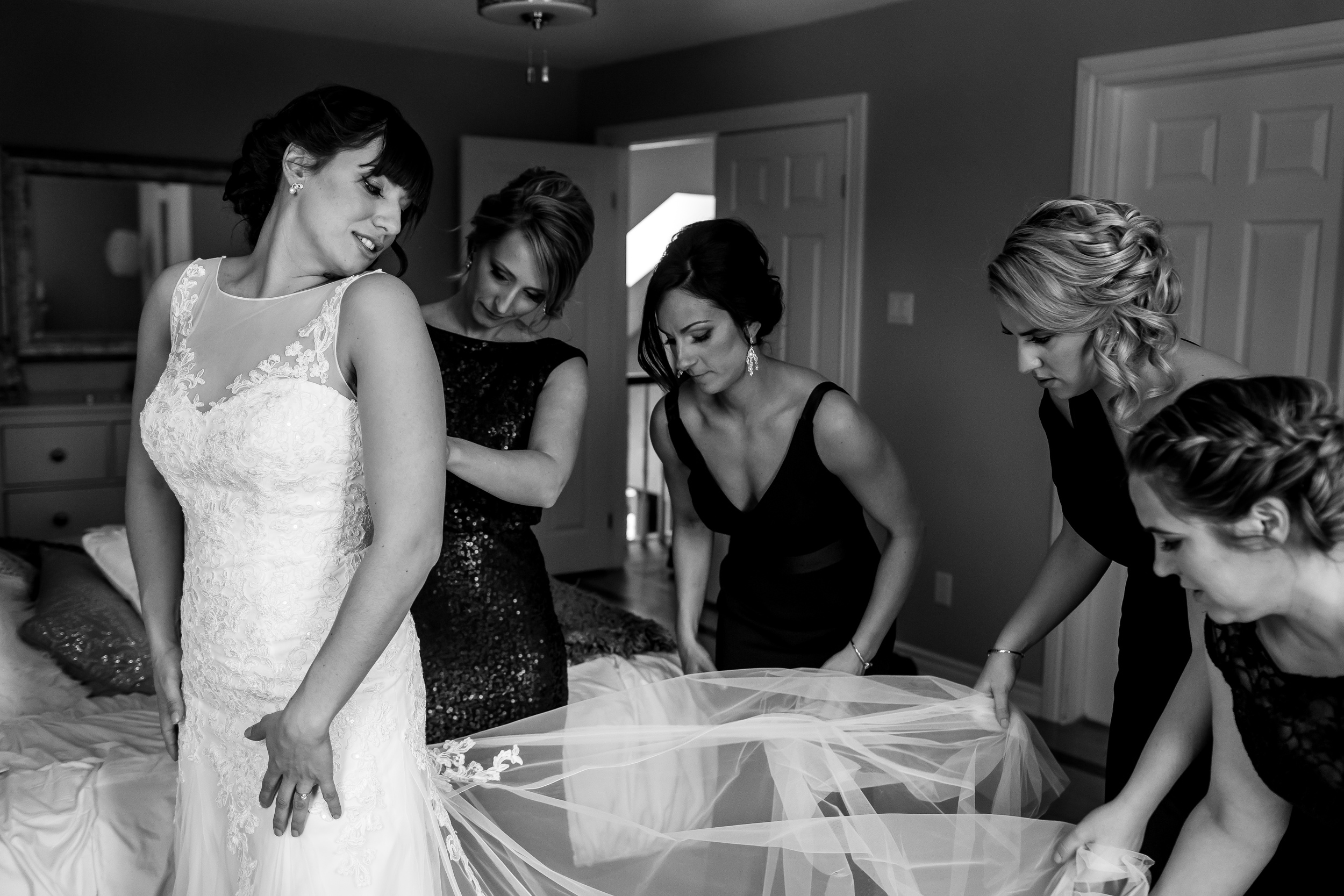 The bridal party helping the bride put on her dress