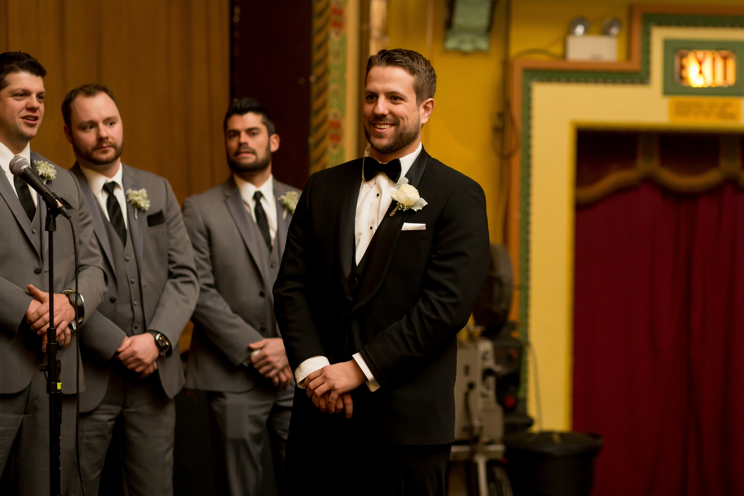 The groom waiting at the alter watching the bride walk down the aisle