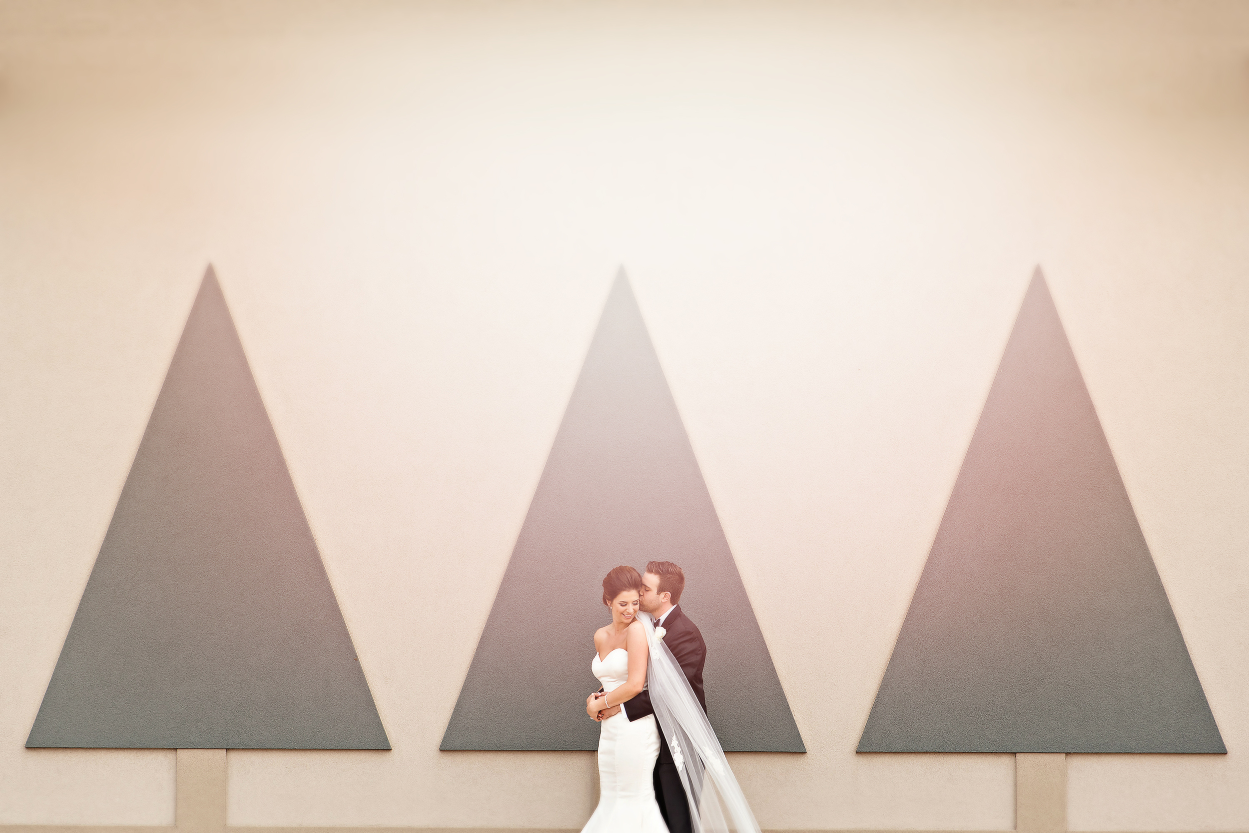 bride groom portrait with trees on building