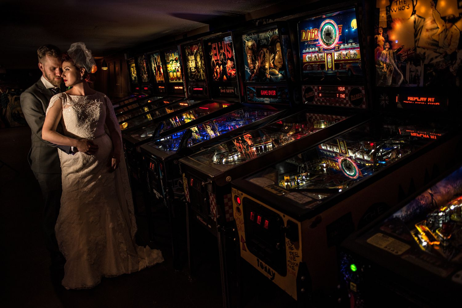 bride and groom portrait by pinball machines at the house of targ