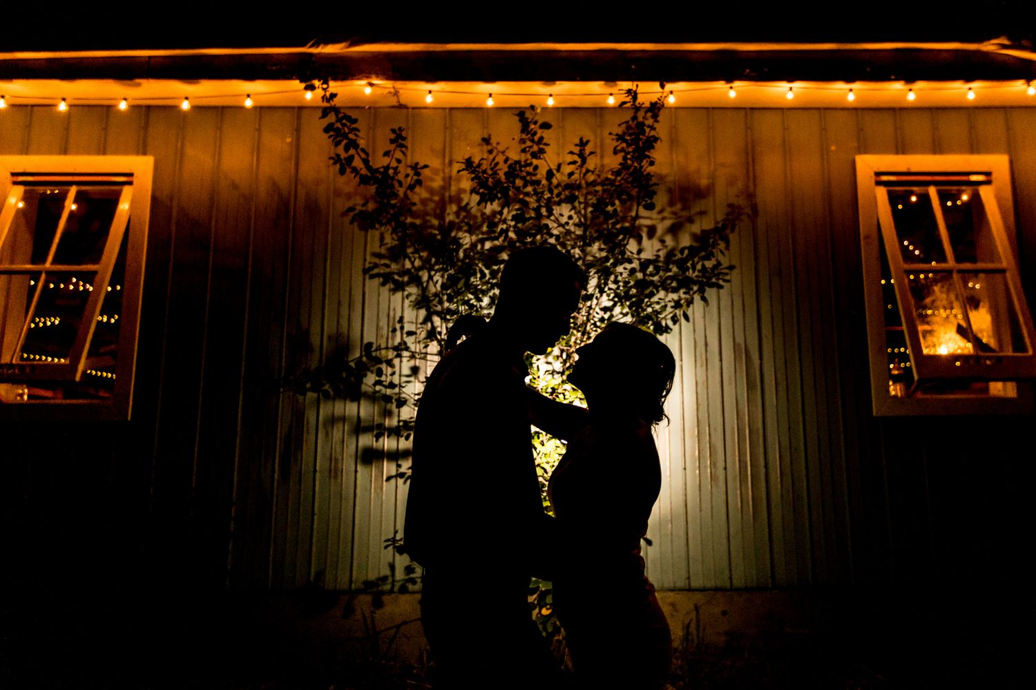 A portrait of the bride and groom at night in front of their newly renovated rustic barn