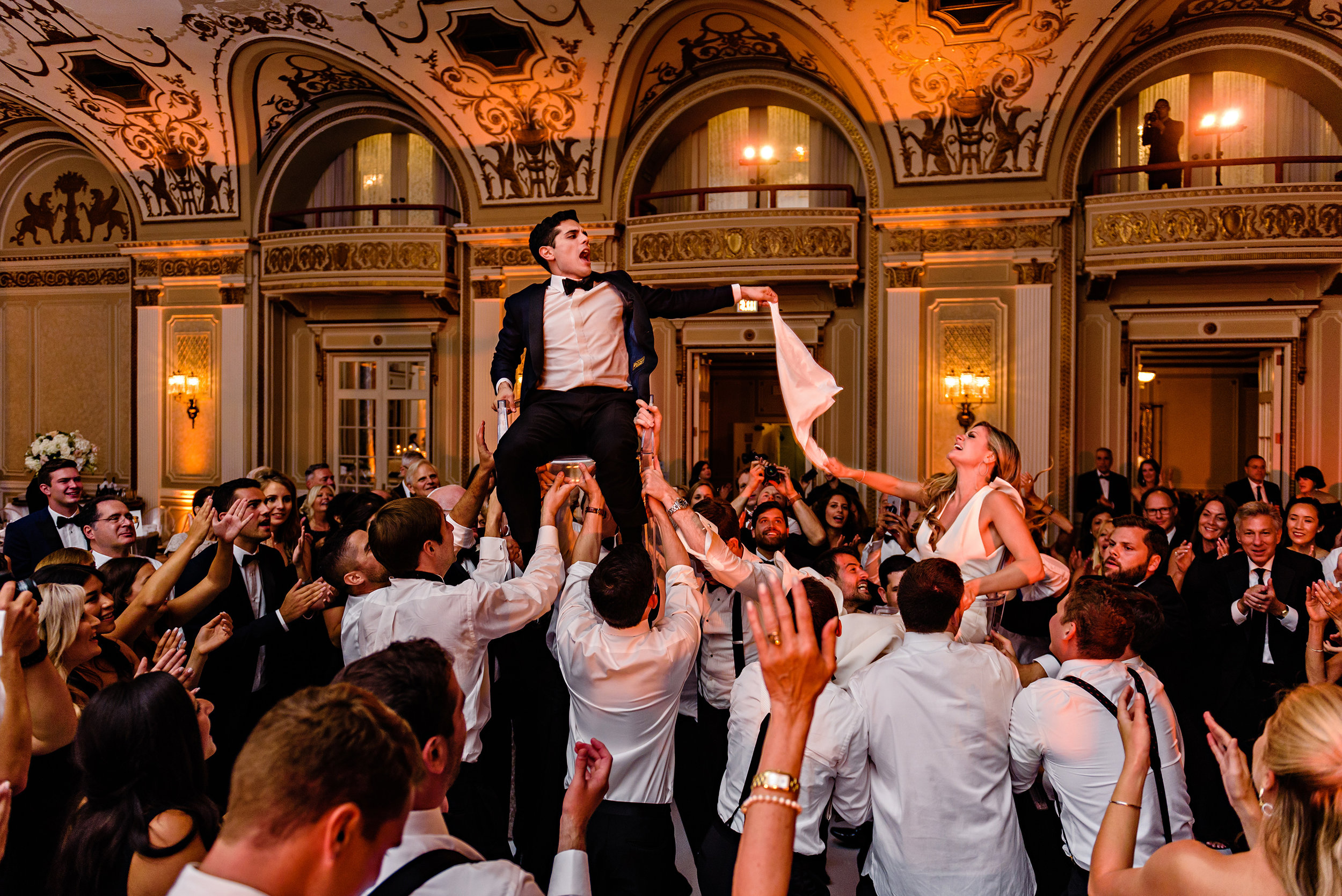 bride-and-groom-high-up-on-chairs-during-a-horah-dance-during-a-wedding-reception-at-a-fairmont-chateau-laurier-in-ottawa.jpg