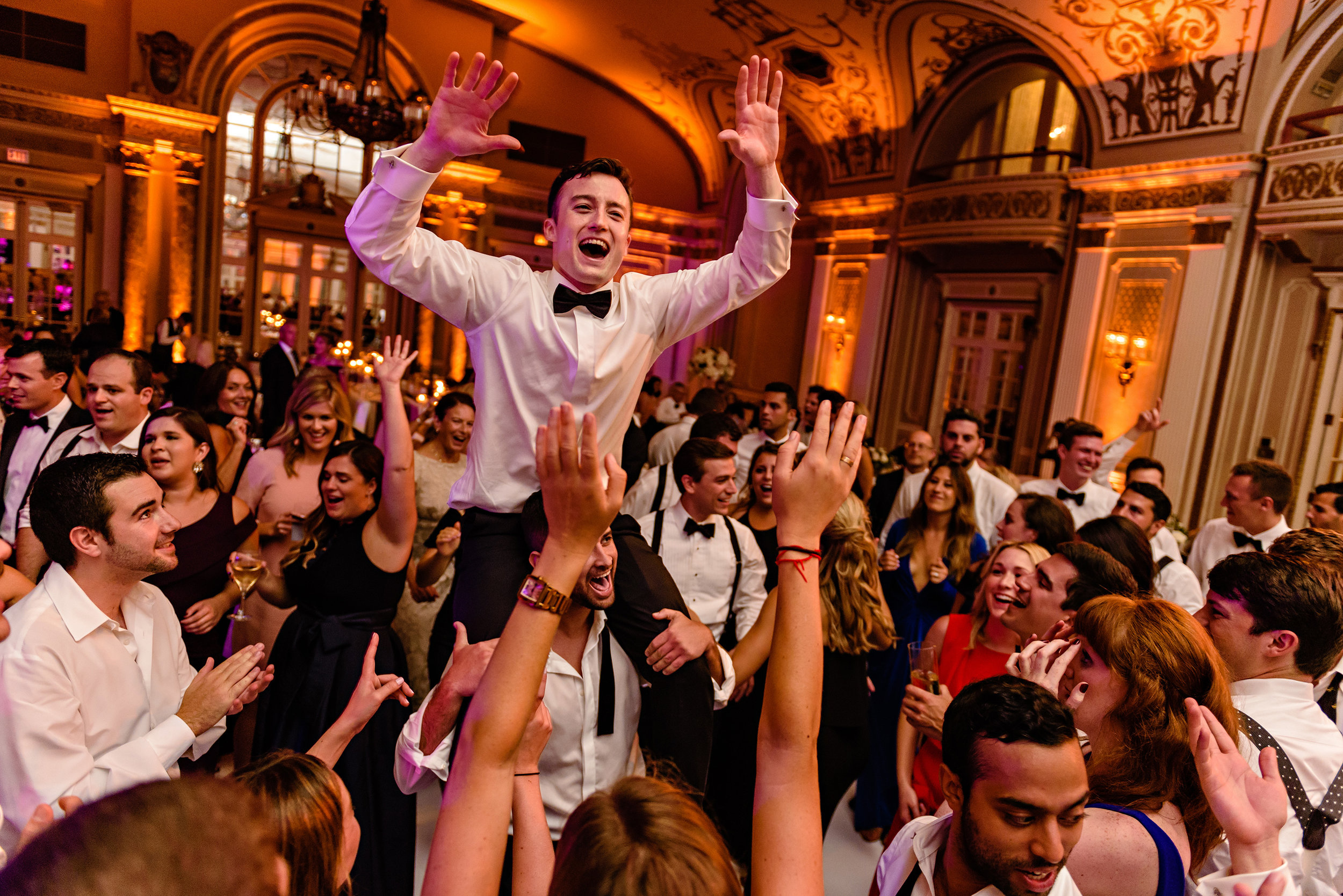 groom-being-lifted-up-during-a-horah-dance-during-a-wedding-reception-at-a-fairmont-chateau-laurier-in-ottawa.jpg