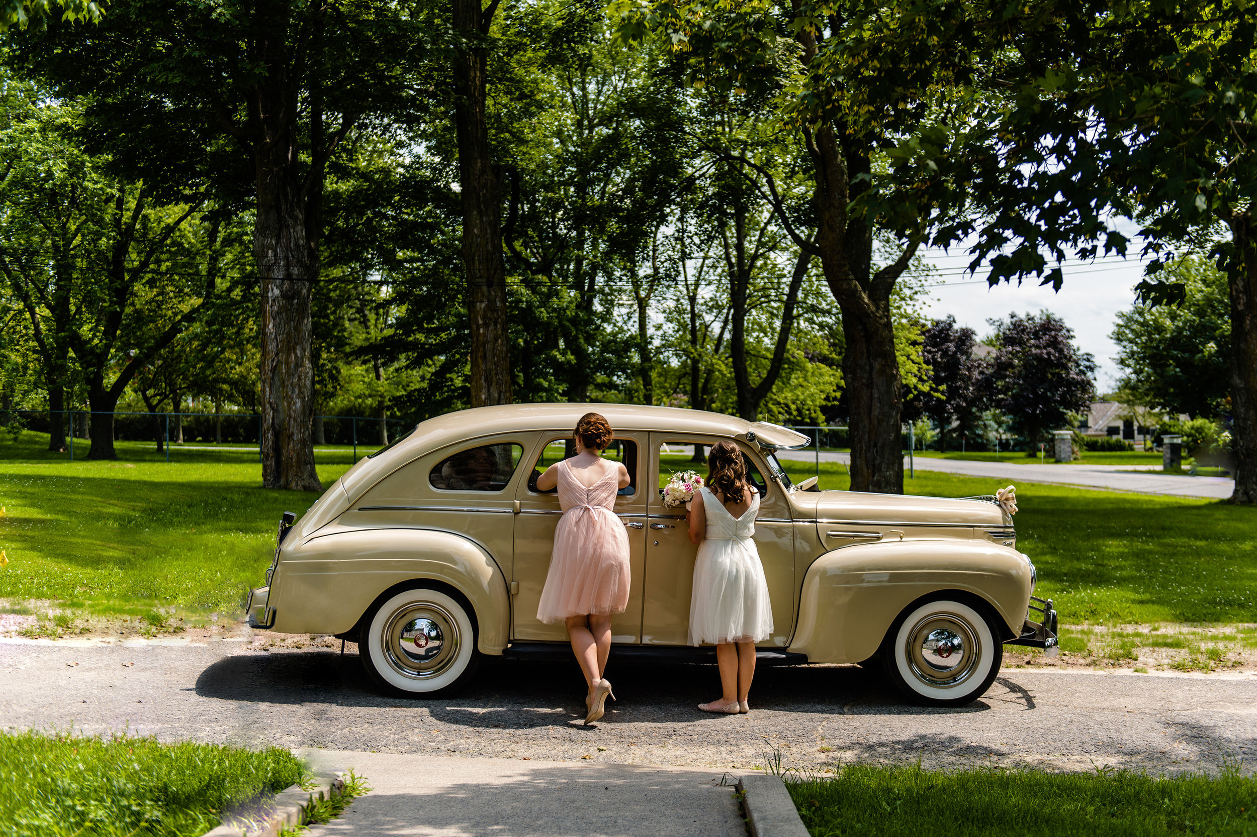bridesmaid-and-flower-girl-look-into-limo-to-check-in-with-bride-before-a-st-patricks-wedding-in-richmond-ontario.jpg