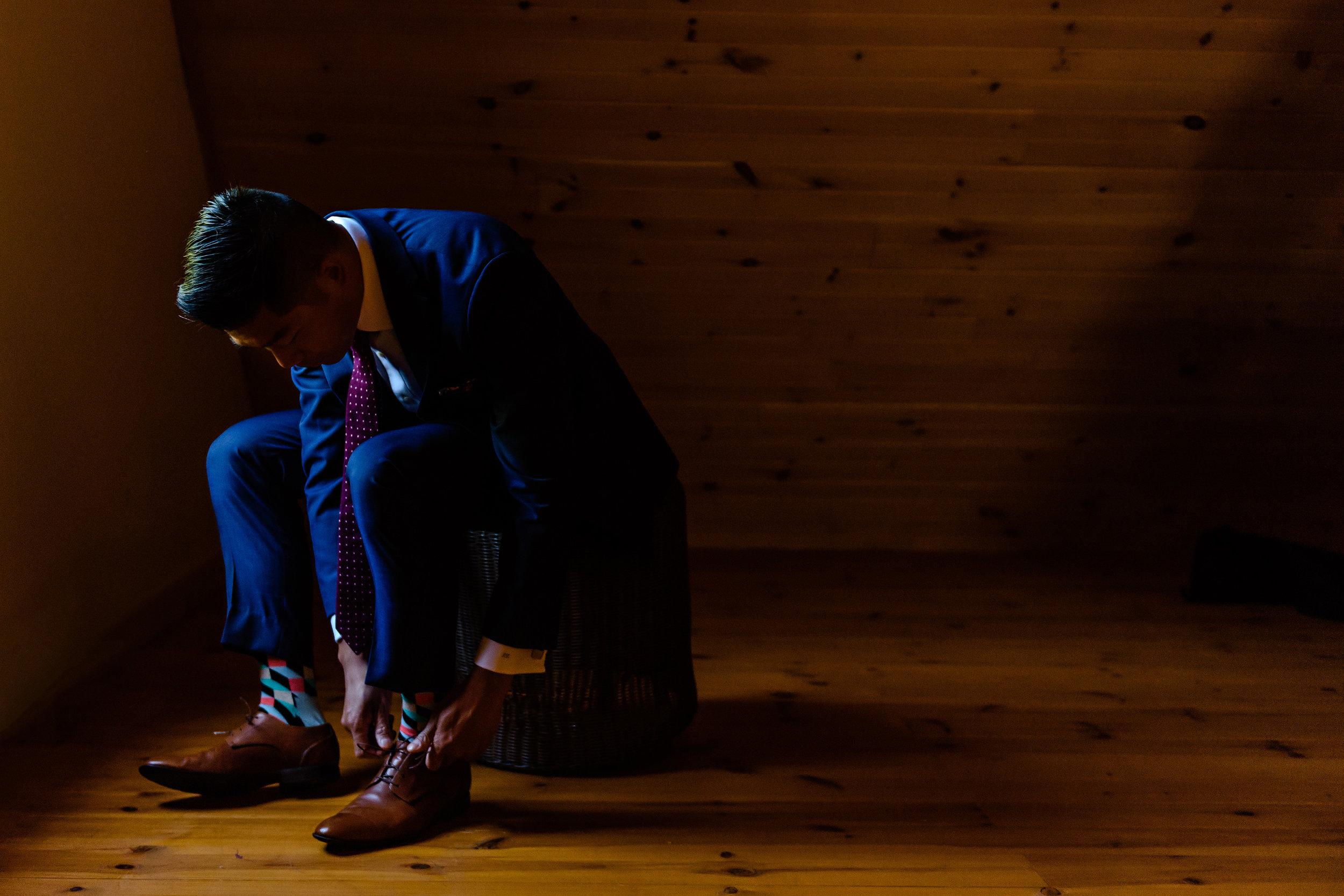 groom-tieing-his-shoe-before-a-le-belvedere-wedding-in-wakefield-quebec.jpg