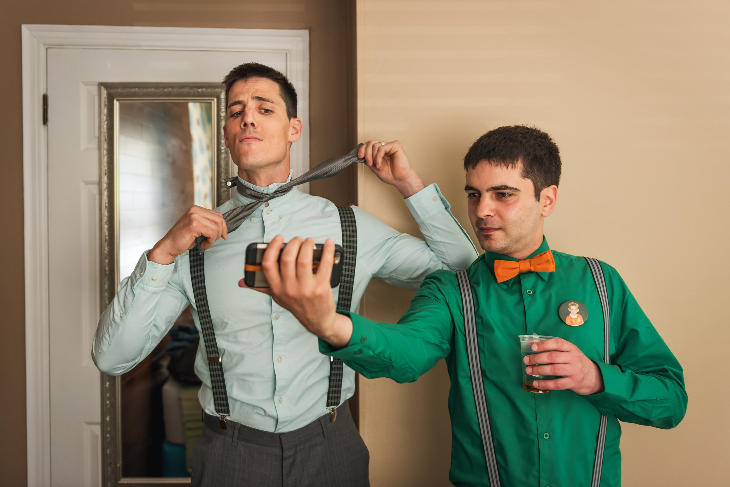 groom-watching-how-to-a-tie-video-while-getting-ready-for-his-museun-of-nature-wedding-in-ottawa-ontario.jpg