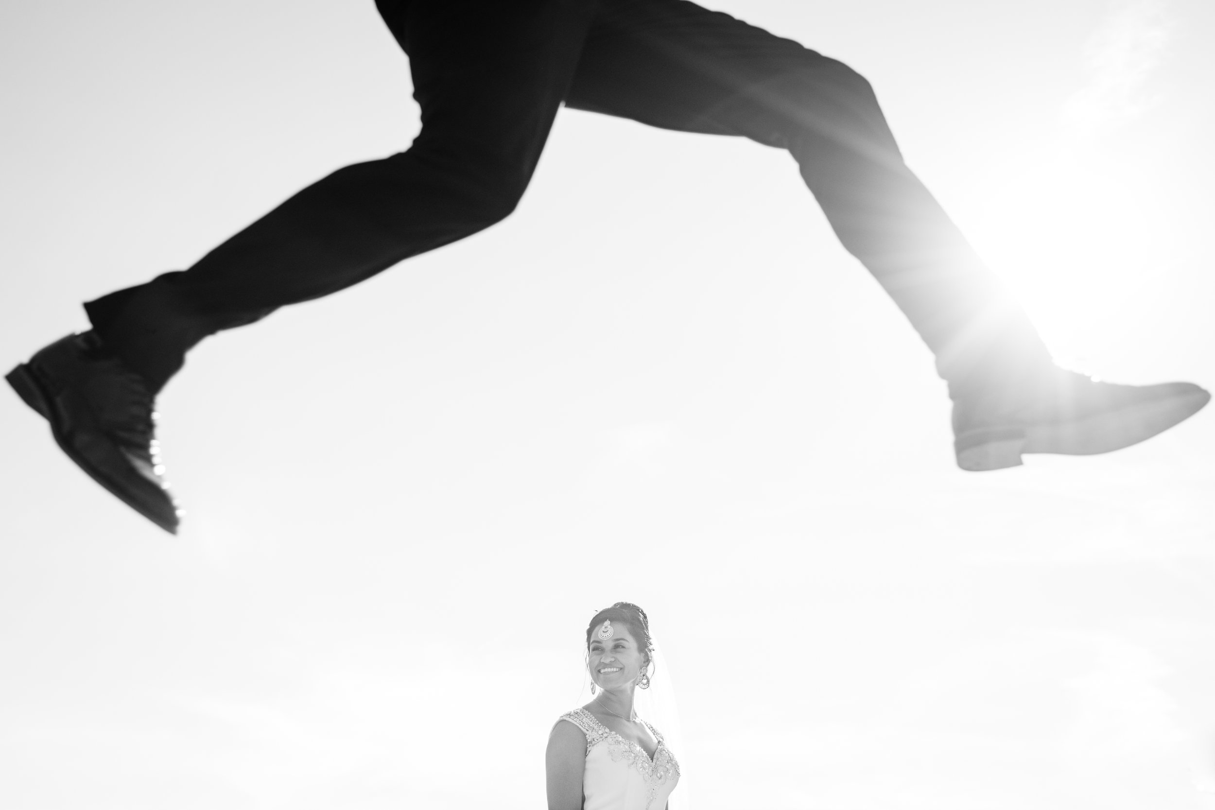 Groom jumping in front bride at le belvedere in Wakefield