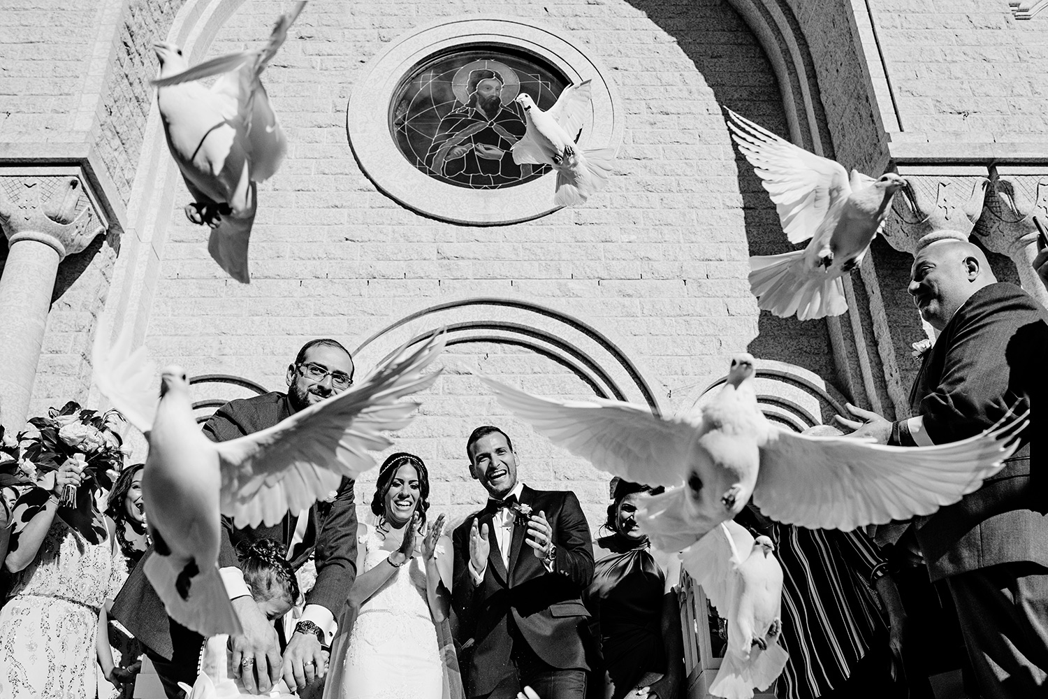 photograph of a bride and groom release doves at the st elias church during a lebanese wedding in ottawa