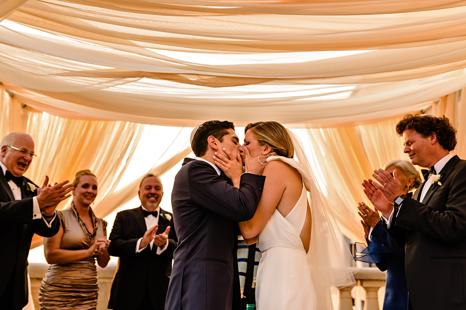 photograph of a bride and groom have their first kiss during a jewish wedding ceremony on the chateau laurier terrace in ottawa ontario
