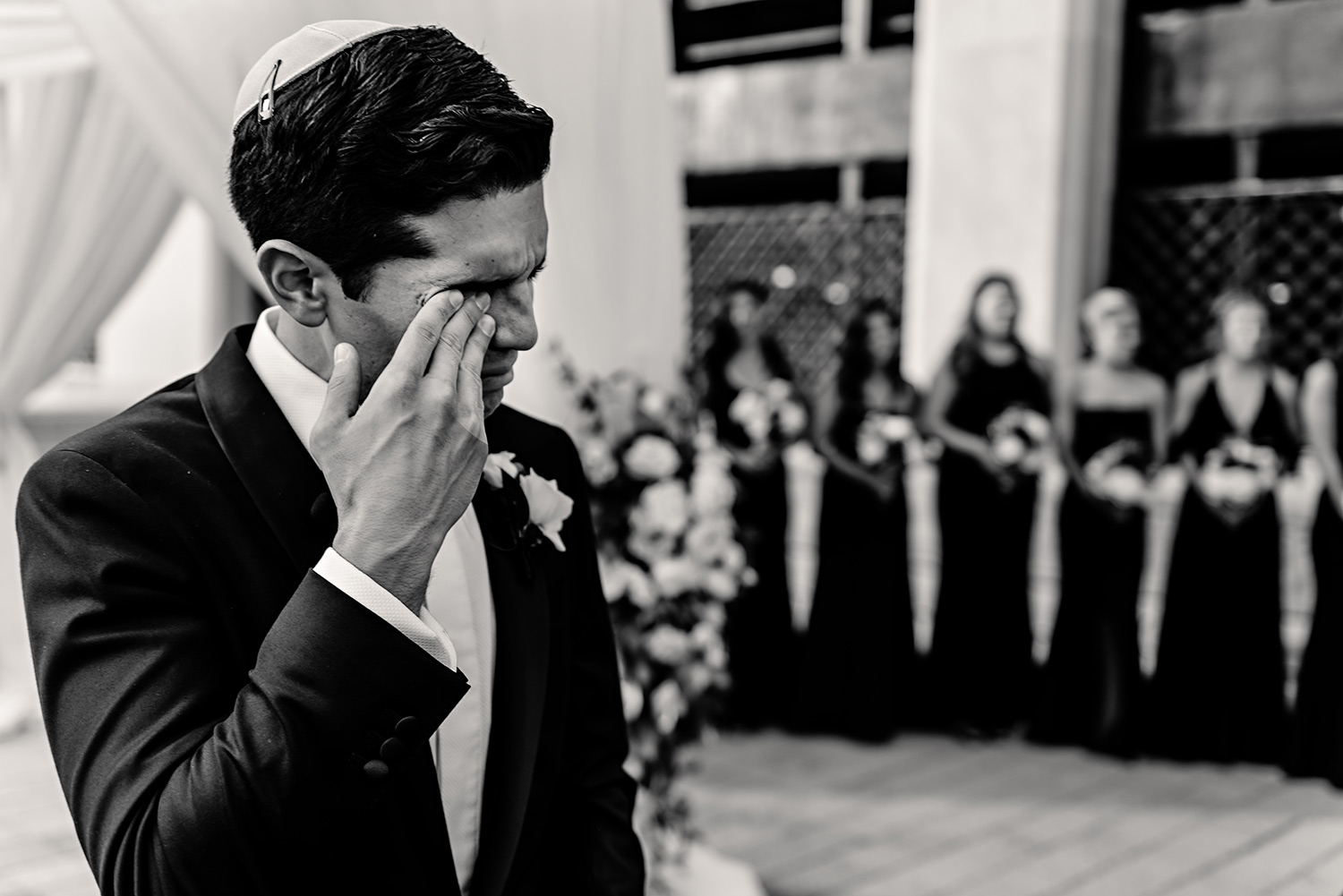 photograph of a groom crying when he see bride come down the aisle at a jewish wedding ceremony at the chateau laurier in ottawa