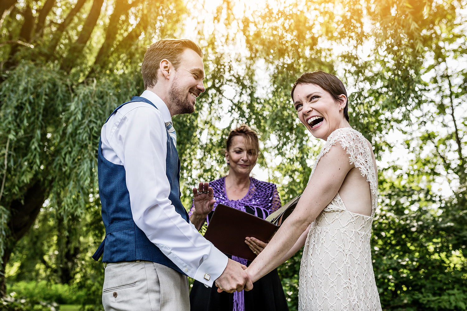 photograph of a bride and groom reacting to vows during a wedding ceremony at experimental farm ottawa