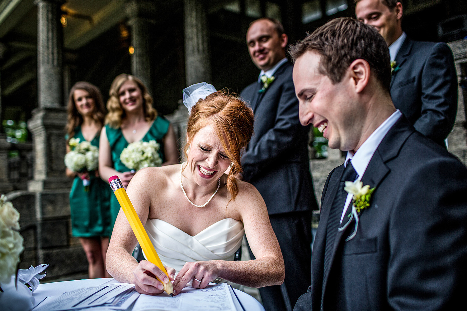 bride signs wedding license with big pencil during a ceremony at the rockcliffe park pavillion ottawa