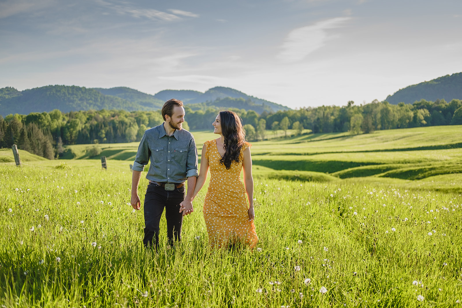country couple pose for enagement photo in a beautiful farm field